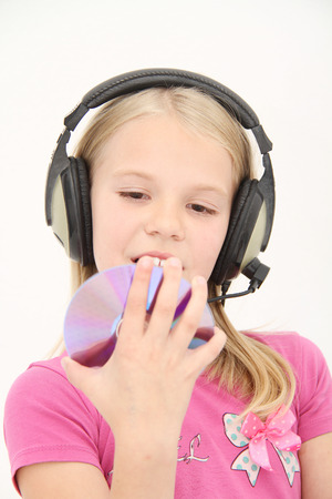Cute little girl is enjoying music using headphones photo