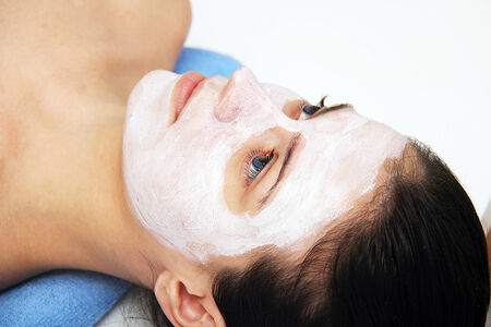 Beautiful young woman with clay facial mask photo