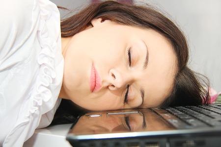 Tired business woman fell asleep next to a laptop Standard-Bild