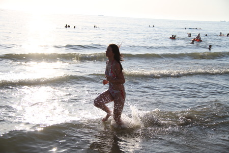 eastern european ethnicity: Young attractive woman running along the seashore
