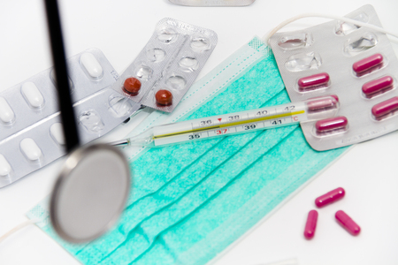 Photo of the Set for flu treatment -  pills, thermometer, nasal sprays, protective surgical mask, stethoscope, syringe...