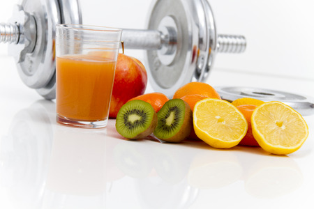 Photo of the Fitness equipment and healthy food, apple, nectarines, kiwi, lemon, juice, dumbbells  and measuring tape photo