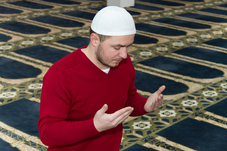 middle eastern clothes: Photo of the Muslim Man Is Praying In The Mosque