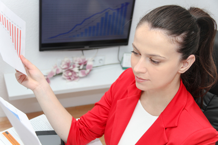 equities: Photo of the Pretty Business woman analyzing investment charts with calculator and laptop Stock Photo