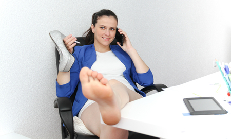 front desk: Photo of the Happy businesswoman sitting with her feet up in her office