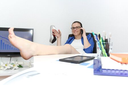 feet on desk: Photo of the Happy businesswoman sitting with her feet up in her office