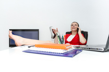 swivel chairs: Photo of the Happy businesswoman sitting with her feet up in her office