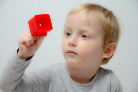 Little boy three years old sits on the table and plays with plasticine and wooden and plastic toys, cubes and dice