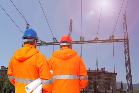 Two electrical engineers in substation, back view