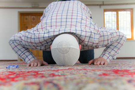 Young muslim man praying inside of beautiful mosque