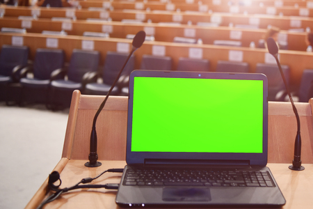 Front view of the laptop and microphones during business conference in conference room or hall, panel duscusion of economic development Stock Photo