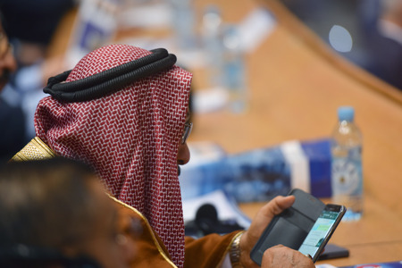 Business Conference and Presentation,Arabic businessman using phone during  representation the  model of economic development and startup business, Audience at the conference hall Stock Photo