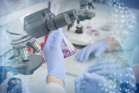 Two young Laboratory scientists working at lab with test tubes and microscope, test or research in clinical laboratory.Science, chemistry, biology, medicine and people concept.