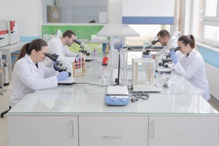 Group of young Laboratory scientists working at lab with test tubes and microscope, test or research in clinical laboratory.Science, chemistry, biology, medicine and people concept.