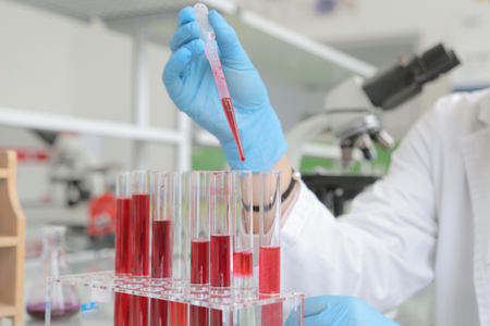 Young female Laboratory scientist working at lab with test tubes and microscope, test or research in clinical laboratory.Science, chemistry, biology, medicine and people concept.