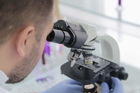 Young male male scientist looking through a microscope in a laboratory doing research, microbiological analysis, medicine.