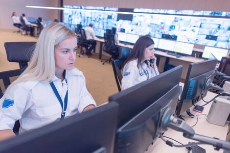 Security guard monitoring modern CCTV cameras in surveillance room. Group of Female security guards in surveillance room.
