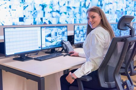 Security guard monitoring modern CCTV cameras in surveillance room. Female security guard in surveillance room. Smiling into camera.