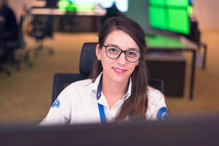 Security guard monitoring modern CCTV cameras in surveillance room. Female security guard in surveillance room. Smiling into camera. Banque d'images