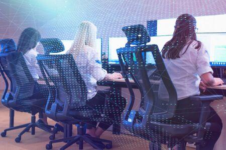 Groupe d'agents de sécurité travaillant sur des ordinateurs assis dans la salle de contrôle principale, surveillance CCTV.