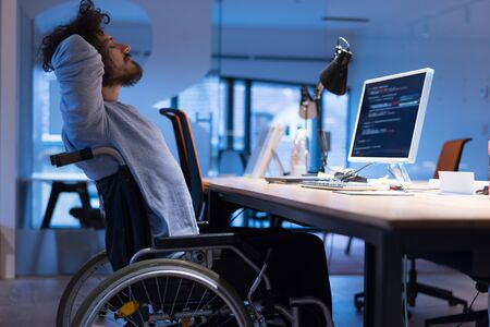 Disabled web developer in the wheelchair works in the office at the computer while performing in co-working space. Disability and handicap concept. Horizontal shot. Selective focus.