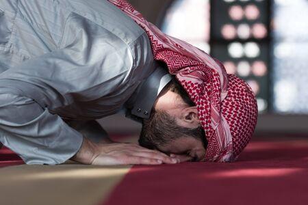 Young Arabic Muslim man praying. Doing a dailly pray inside modern beautiful mosque. Stock Photo