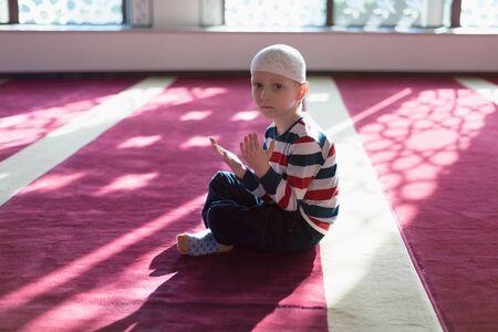 Ramadan Kareem,beautiful boy Muslim is praying in mosque,Peace and love in the holy month of Ramadan