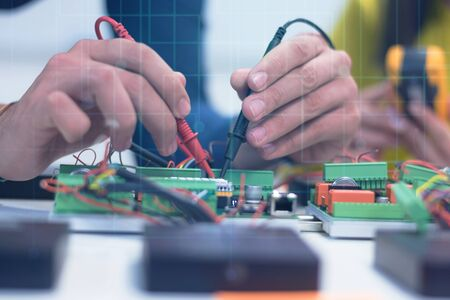 Two young handsome engineers working on electronics components.Tech tests electronic equipment in service center. Technologically Advanced Scientific Research Center. Foto de archivo