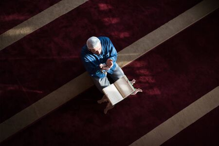 Young Arabic Muslim man reading Koran and praying. Religious muslim man reading holy koran inside the mosque.