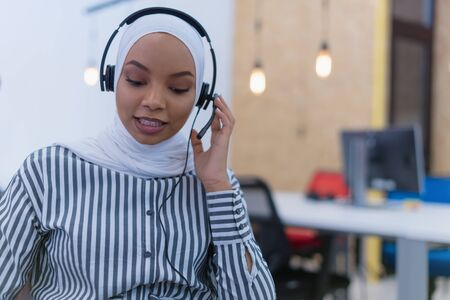 Happy african muslim woman in call center. Female Customer Service Representative Answer Client's Questions in a Headset. Multi-Ethnic Team of Specialists.