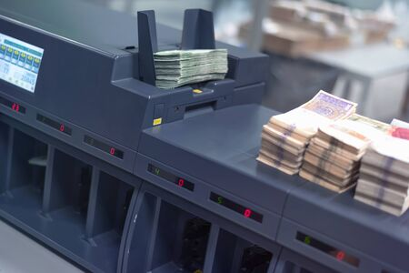 Bundles of banknotes divided into groups with currency straps placed on the electronic counting machine