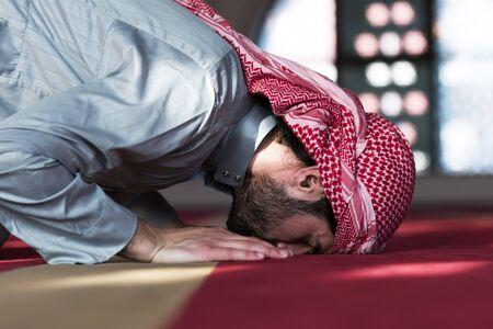 Young Arabic Muslim man  praying. Doing a dailly pray inside modern beautiful mosque.