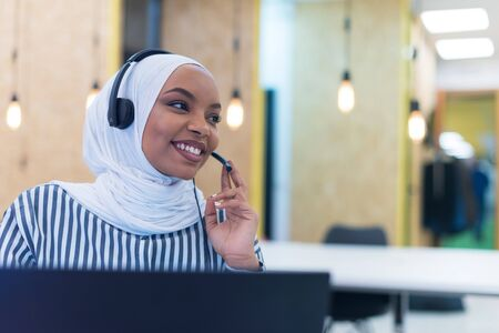 African muslim female with hijab scarf customer representative business woman with phone headset helping and supporting online with customer in modern bright call centre. Standard-Bild