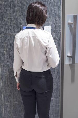 Businesswoman bank employee  bank vault door typing security code for alarm system.