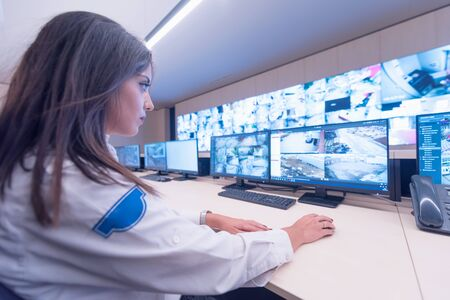 Security guard monitoring modern CCTV cameras in surveillance room. Female security guard in surveillance room.