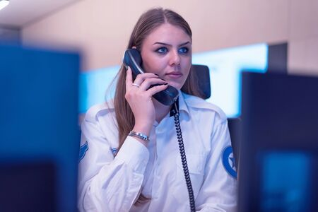 Female security guard operator talking on the phone, calling in the alarming event to the external team of field force agents.