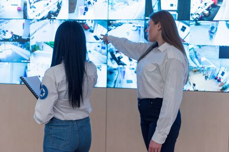 Security guard monitoring modern CCTV cameras in surveillance room. Two Female security guards in surveillance room.