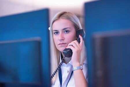 Female security guard operator talking on the phone, calling in the alarming event to the external team of field force agents. Фото со стока