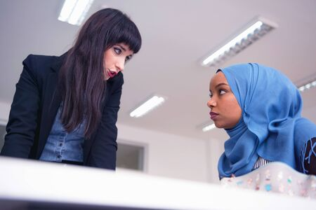 Female Architecture teacher at work. Female professor explain architectural projects to female african student.