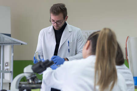 Group of  Laboratory scientists working at lab with test tubes, test or research in clinical laboratory.Science, chemistry, biology, medicine and people concept. Standard-Bild