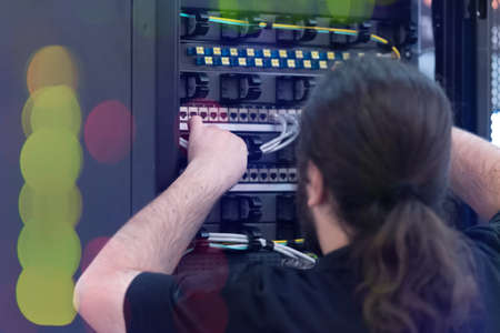 An Expert Engeneer in datacenter server room connecting cables in server cabinet in network server room.