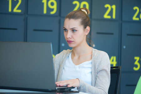 Attractive young woman using laptop while sitting at her desk. Young american businesswoman sitting in the office and working on laptop.