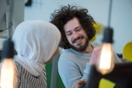 Smiling african muslim business woman talking to male colleague at work sharing office desk with desktops, friendly multiracial coworkers interns having pleasant fun conversation at workplace together