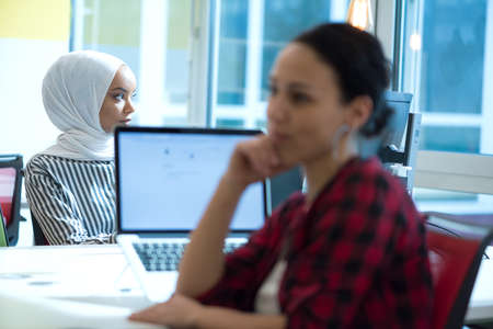 Pretty african muslim business womanand her female american colleague at work sharing office desk with desktops, friendly multiracial coworkers interns having pleasant at workplace together Standard-Bild