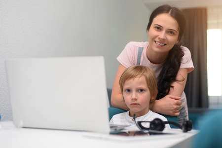 Coronavirus Outbreak. Lockdown and school closures. Mother helping her son studying online classes at home. COVID-19 pandemic forces children and teachers online learning.