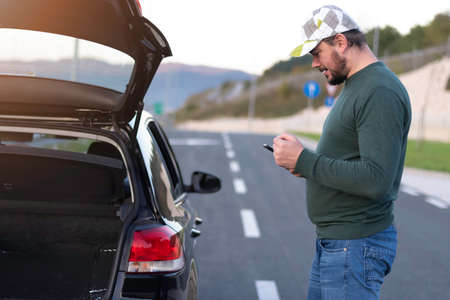 Man calling road assistance on the highway. Calling car service, assistance or tow truck while having troubles with his car.