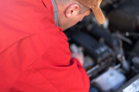 Emergency roadside assistance, road assistance worker in uniform trying to fix car breakdown or engine failure.  Roadside assistance concept 免版税图像