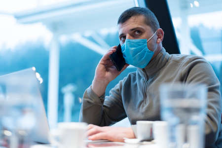 Businessman in medical mask during quarantine. A young man in a cafe works at a laptop by the window.
