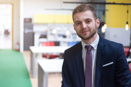 Portrait of young bearded Caucasian businessman dressed smart casual posing inside modern coworking space.