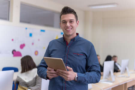 Portrait of casual turkish male student holding tablet or ipad inside modern computerlab classroom. Technology and education concept Standard-Bild